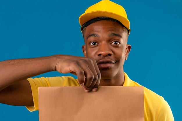 Uomo afroamericano di consegna in camicia di polo gialla e cappuccio che tiene il pacchetto di carta sorridente amichevole sul blu isolato