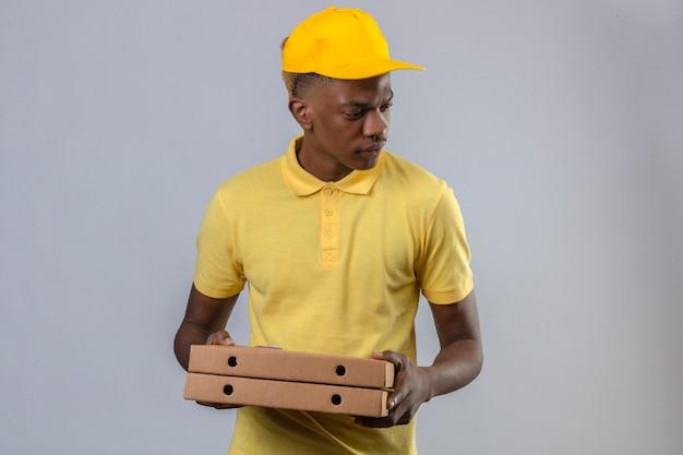 Consegna uomo afroamericano in maglietta polo gialla e berretto tenendo scatole per pizza guardando da parte con faccia accigliata in piedi