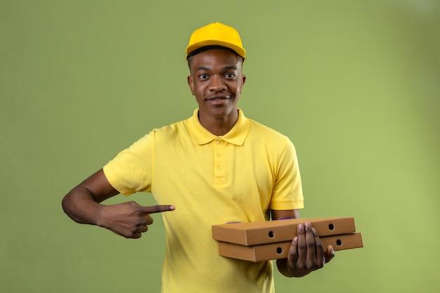 Consegna uomo afroamericano in maglietta polo gialla e berretto in possesso di scatole per pizza e indicando con il dito a lato sorridente in piedi amichevole sul verde isolato