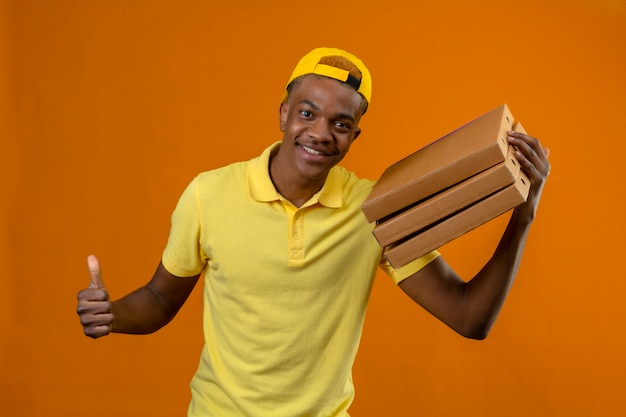 Delivery african american man in yellow polo shirt and cap holding pizza boxes showing thumb up with happy face on isolated orange