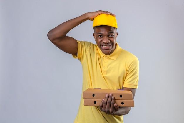 Consegna uomo afroamericano in maglietta polo gialla e berretto tenendo scatole per pizza ha sottolineato in piedi con la mano sulla testa scioccato dalla vergogna
