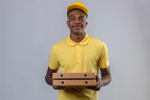 Consegna uomo afroamericano in maglietta polo gialla e cappuccio che tiene scatole per pizza con sorriso fiducioso in piedi