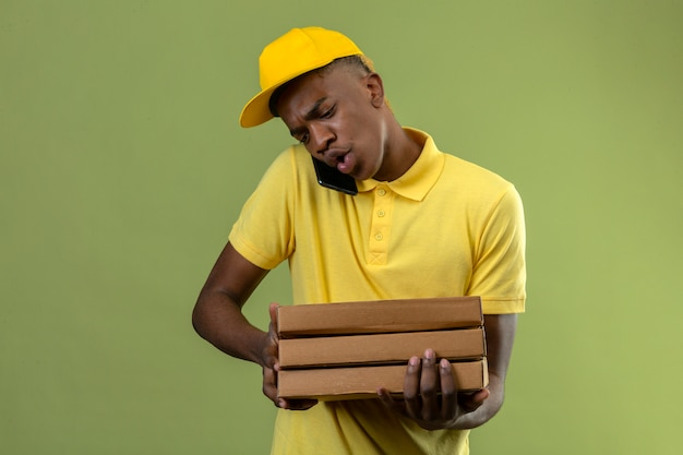 Delivery african american man in yellow polo shirt and cap holding stack of pizza boxes while talking on mobile phone looking surprised standing on green