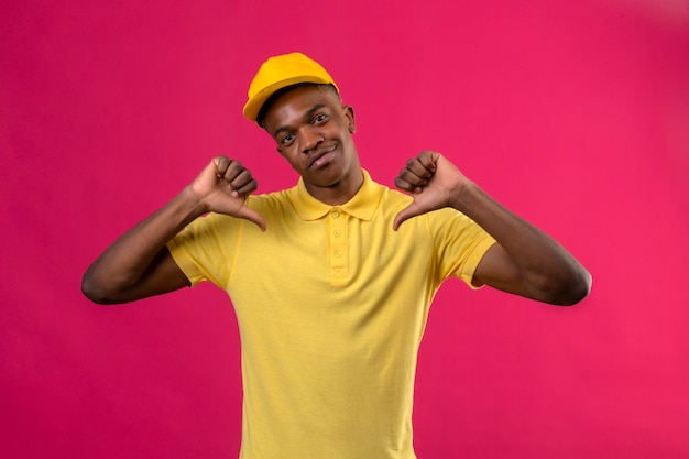 Delivery african american man in yellow polo shirt and cap looking confident pointing to himself proud self-satisfied standing on pink