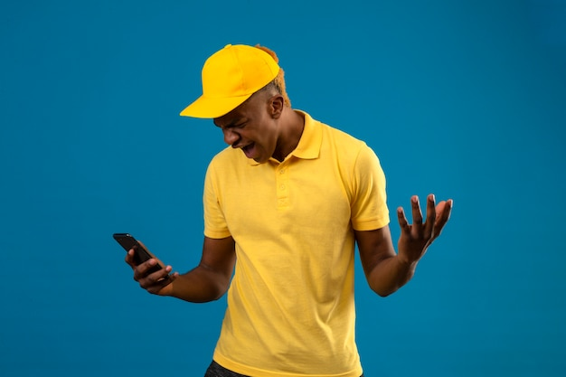 Delivery african american man in yellow polo shirt and cap looking at mobile phone with angry expression raising hands frustrated standing on isolated blue