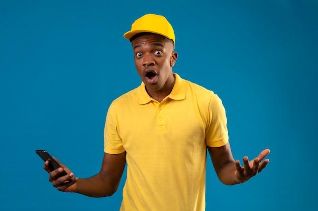 Consegna uomo afroamericano in maglietta polo gialla e berretto palmi sparsi scioccati in piedi sul blu isolato