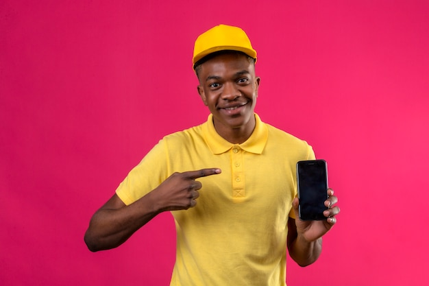 Delivery african american man in yellow polo shirt and cap smiling cheerfully pointing with finger to smartphone in his hand on pink