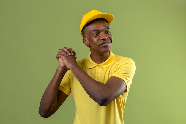 Delivery african american man in yellow polo shirt and cap smiling holding hands together grateful gesture standing on green
