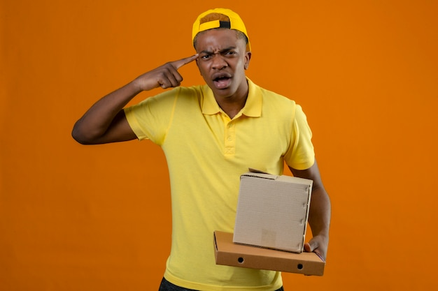 Delivery african american man in yellow polo shirt and cap standing with cardboard boxes pointing temple with finger with angry expression on face on isolated orange