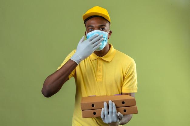 Consegna uomo afroamericano in maglietta polo gialla e berretto che indossa la maschera protettiva medica tenendo scatole per pizza guardando sorpreso coning bocca con la mano in piedi sul verde