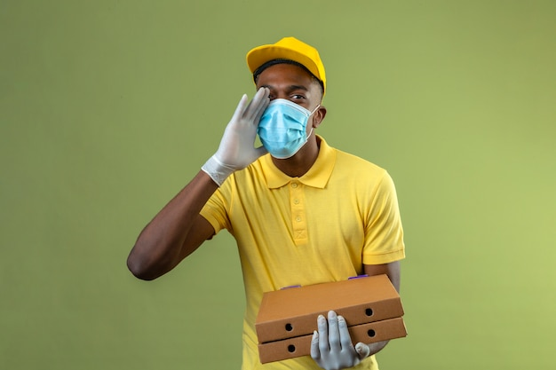 Delivery african american man in yellow polo shirt and cap wearing medical protective mask holding pizza boxes shouting or calling someone with hand near mouth standing on green