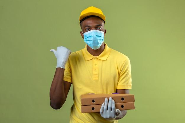 Consegna uomo afroamericano in maglietta polo gialla e berretto indossando maschera protettiva medica che tiene scatole per pizza con faccia seria che punta di lato con il pollice in piedi sul verde