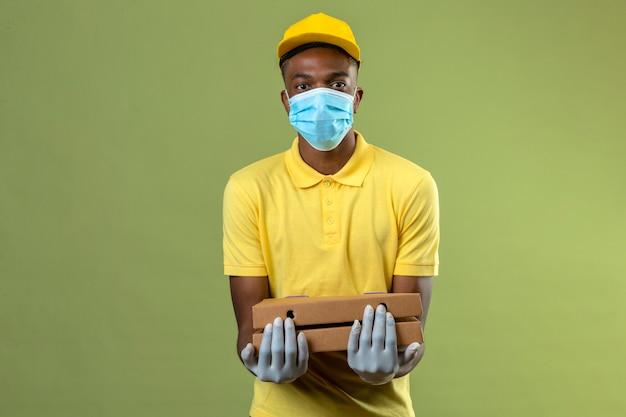 Consegna uomo afroamericano in maglietta polo gialla e berretto indossando maschera protettiva medica che tiene scatole per pizza con faccia seria in piedi sul verde