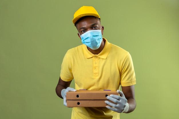 Consegna uomo afroamericano in maglietta polo gialla e berretto indossando maschera protettiva medica che tiene scatole per pizza con il sorriso sul viso in piedi sul verde
