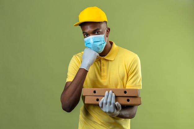Consegna uomo afroamericano in maglietta polo gialla e berretto indossando maschera protettiva medica sorridendo e toccando il mento sul verde isolato