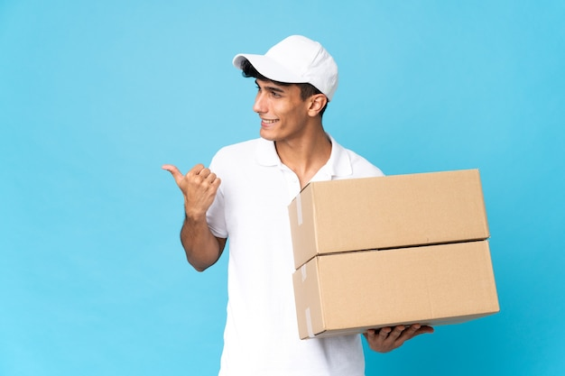 Delivery argentinian man isolated on blue background pointing to the side to present a product