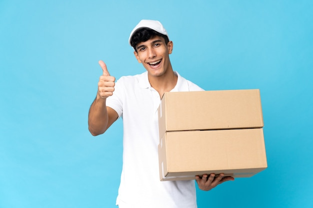 Delivery argentinian man isolated on blue background with thumbs up because something good has happened