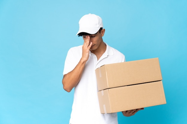 Delivery argentinian man isolated on blue background with tired and sick expression