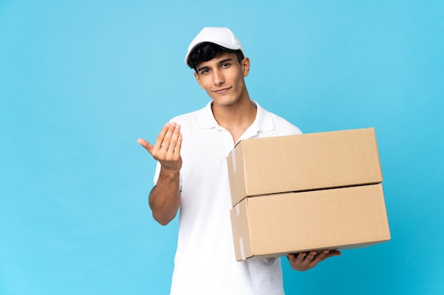 Delivery argentinian man isolated on blue surface inviting to come with hand. happy that you came