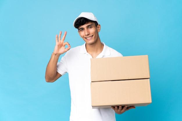 손가락으로 확인 표시를 보여주는 파란색 배경에 고립 배달 아르헨티나 남자