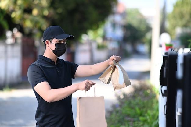 배달 아시아 남자는 보호 마스크를 착용하고 출입구에서 음식을 배달합니다.