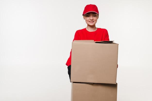 Доставка азиатская женщина в красной униформе изолирована женщина в джинсах с кепкой работает курьером или дилером, держащим картонную коробку.