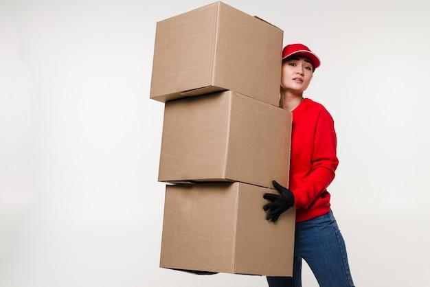 白い壁に分離された赤い制服を着た配達アジアの女性宅配便または段ボール箱を保持しているディーラーとして働くキャップtシャツジーンズの女性