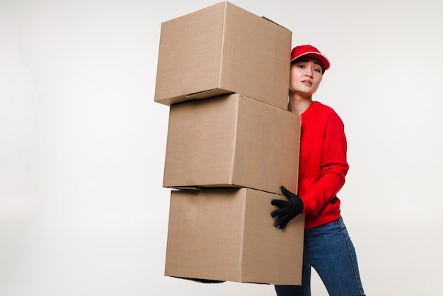 Delivery asian woman in red uniform isolated on white wall female in cap t-shirt jeans working as courier or dealer holding cardboard box