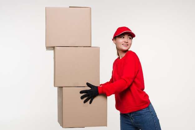 Delivery asian woman in red uniform isolated on white wall female in cap tshirt jeans working as courier or dealer holding cardboard box receiving package