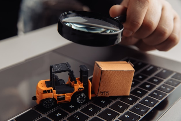 Delivery box, model of loader and a magnifying glass. concept of internet commerce, online shopping, trade and turnover.