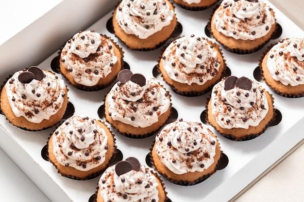 モカバタークリームとチョコレートチップを飾ったコーヒーカップケーキの入った配達箱