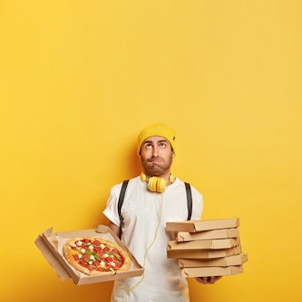 Delivery boy brings cardboard pizza boxes for client, looks upwards, wears yellow hat, white t shirt, works transporting fast food, isolated on yellow wall, copy space for your promotion