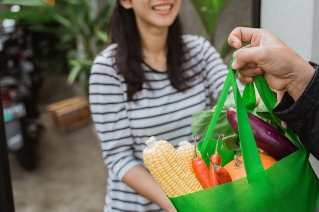 Мальчик доставки доставляет продукты женщине