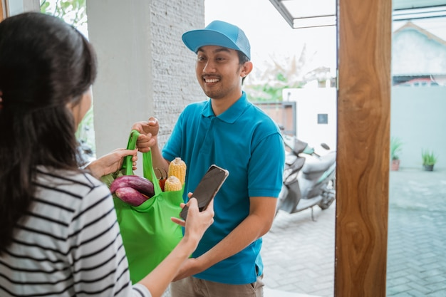 Delivery boy is delivering some groceries to woman
