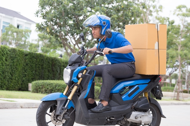 Delivery boy on motorcycle with trunk parcel box driving to fast in rush