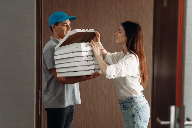 配達の少年は玄関先で女性客に新鮮で熱いピザを示しています