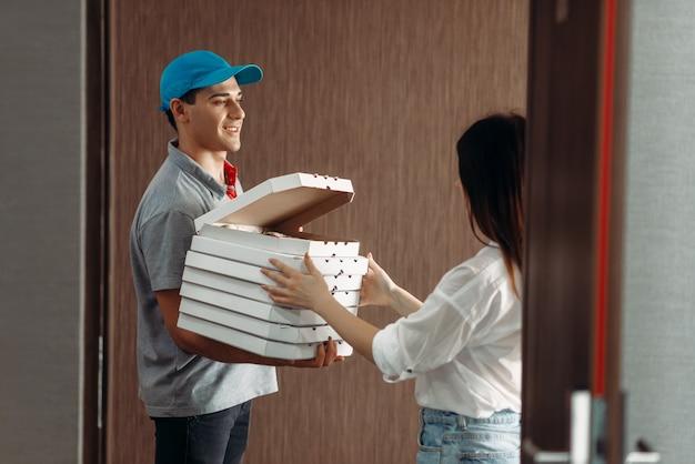 配達の少年は女性客にピザを示しています
