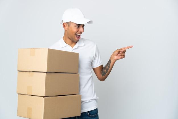Доставка бразильский мужчина изолирован на белой стене, указывая пальцем в сторону и представляя продукт