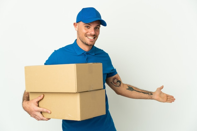 Delivery caucasian man isolated extending hands to the side for inviting to come