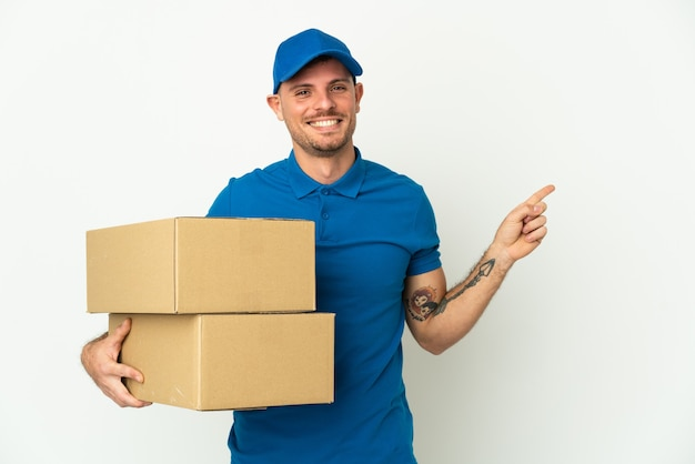 Delivery caucasian man isolated pointing finger to the side