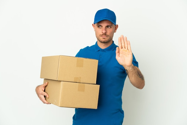 Delivery caucasian man isolated on white background making stop gesture and disappointed