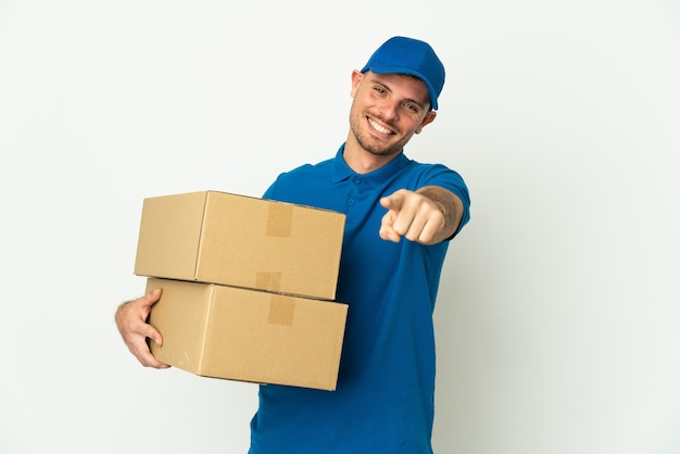 Delivery caucasian man isolated on white background pointing front with happy expression