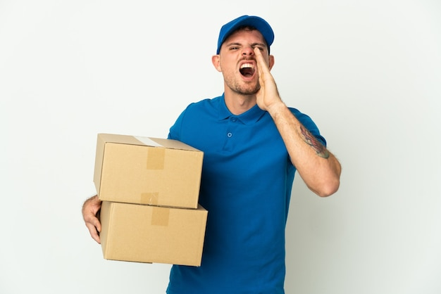 Delivery caucasian man isolated on white background shouting with mouth wide open