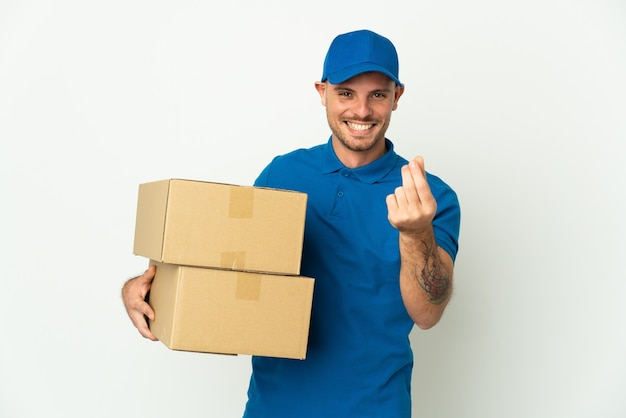 Delivery caucasian man isolated on white wall making money gesture