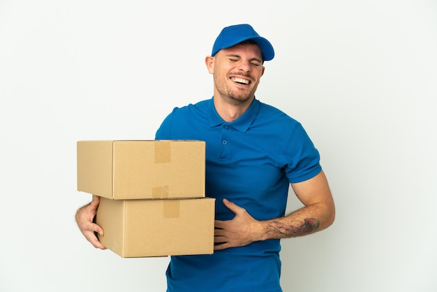 Delivery caucasian man isolated on white wall smiling a lot