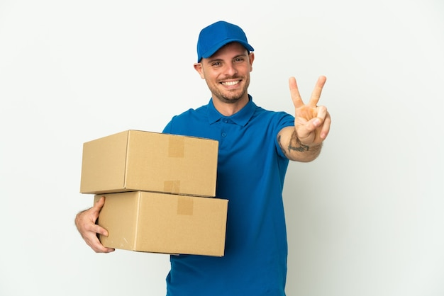 Delivery caucasian man isolated on white wall smiling and showing victory sign