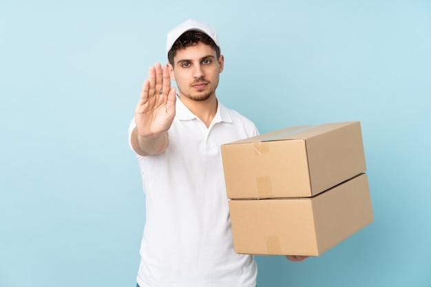 Доставка кавказских человек на синей стене, делая остановки жест рукой