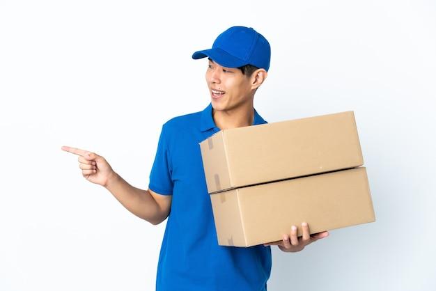 Доставка китаец, изолированные на белом фоне, указывая пальцем в сторону и представляя продукт