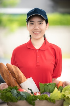 Delivery company worker holding grocery bag, food order, supermarket service, accepting groceries box from delivery woman at home, fresh organic vegetable delivery