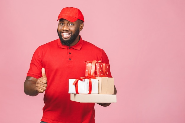 Delivery concept. african american delivery black man carrying parcel and gift boxes. thumbs up.